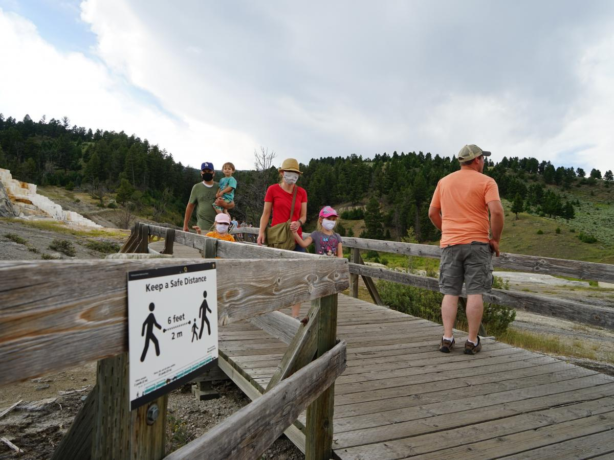 Signs urge people to stay 6 feet apart on a walkway at Yellowstone National Park's Mammoth Hot Springs. But it's difficult to maintain distancing on narrow trails.