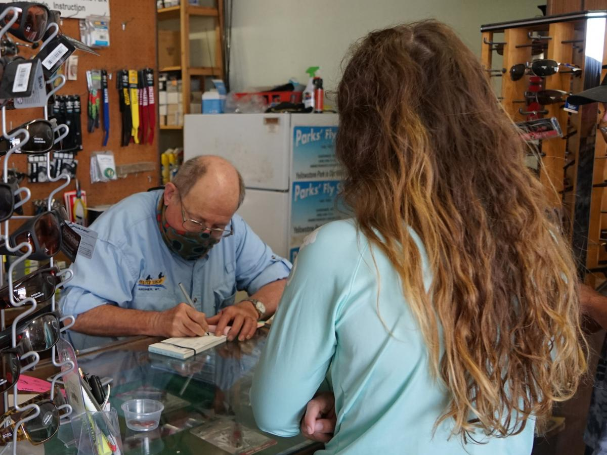 Richard Parks fills out a fishing license for a customer at his shop in Gardiner, Mont. After a slow start to the summer tourism season, he says, business is now booming.