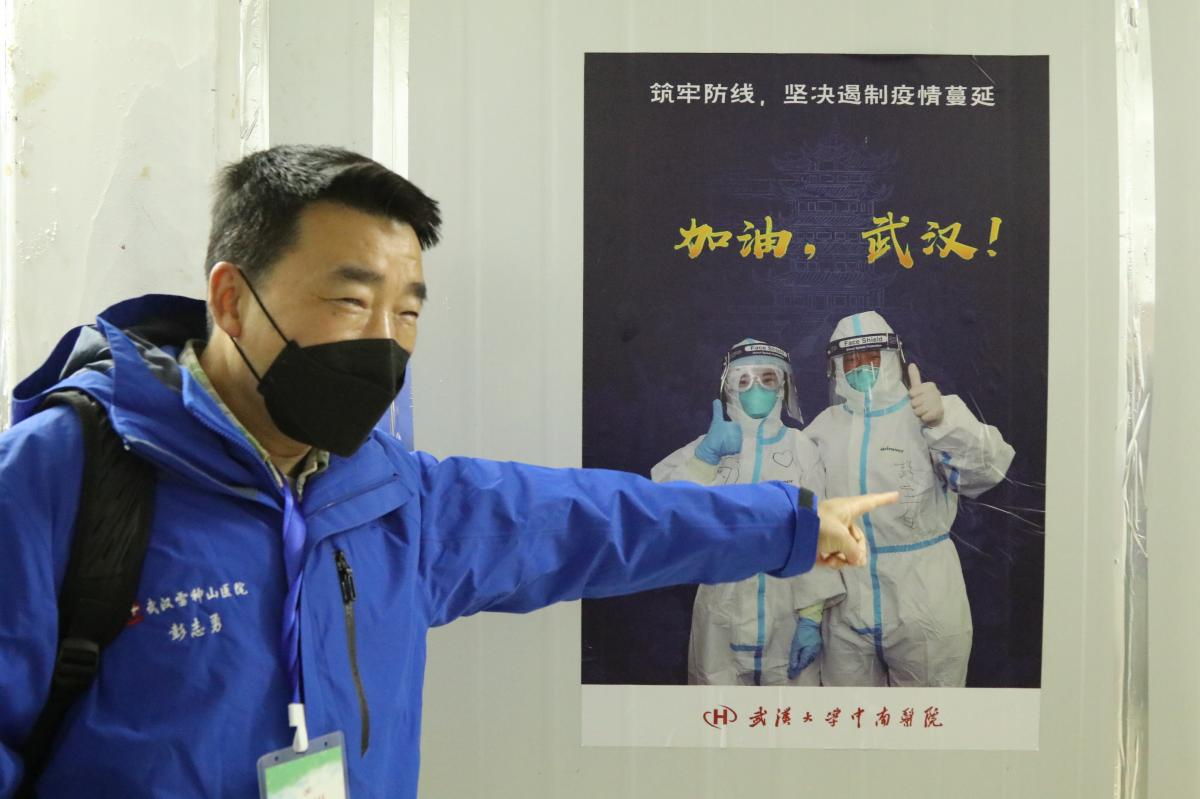 Peng Zhiyong, an intensive care doctor in Wuhan, points to a picture of himself on a poster in Leishenshan Hospital, a temporary facility built to treat COVID-19 patients.