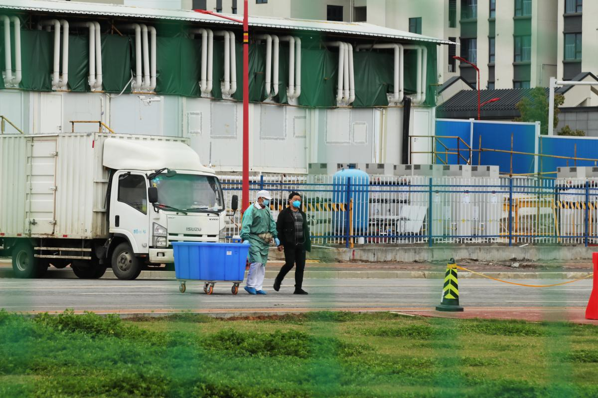 Staff members walk near the Leishenshan Hospital. The facility was built in February to handle the overflow from Wuhan hospitals overwhelmed by coronavirus patients.