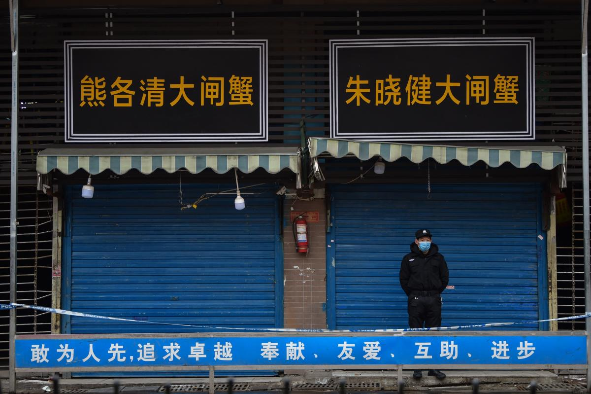 A security guard stands outside the Huanan Seafood Wholesale Market, where the coronavirus was detected in Wuhan.