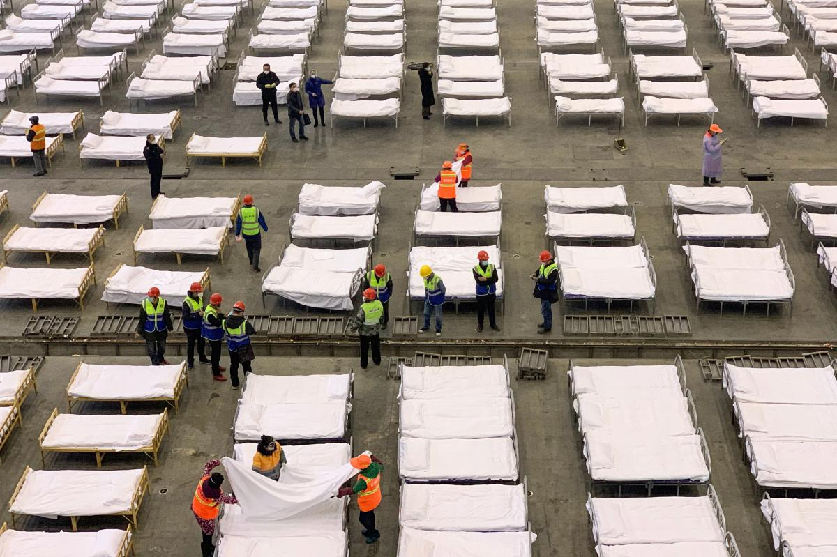 Workers set up beds at an exhibition center that was converted into a hospital in Wuhan, in China's central Hubei province, on Feb. 4.