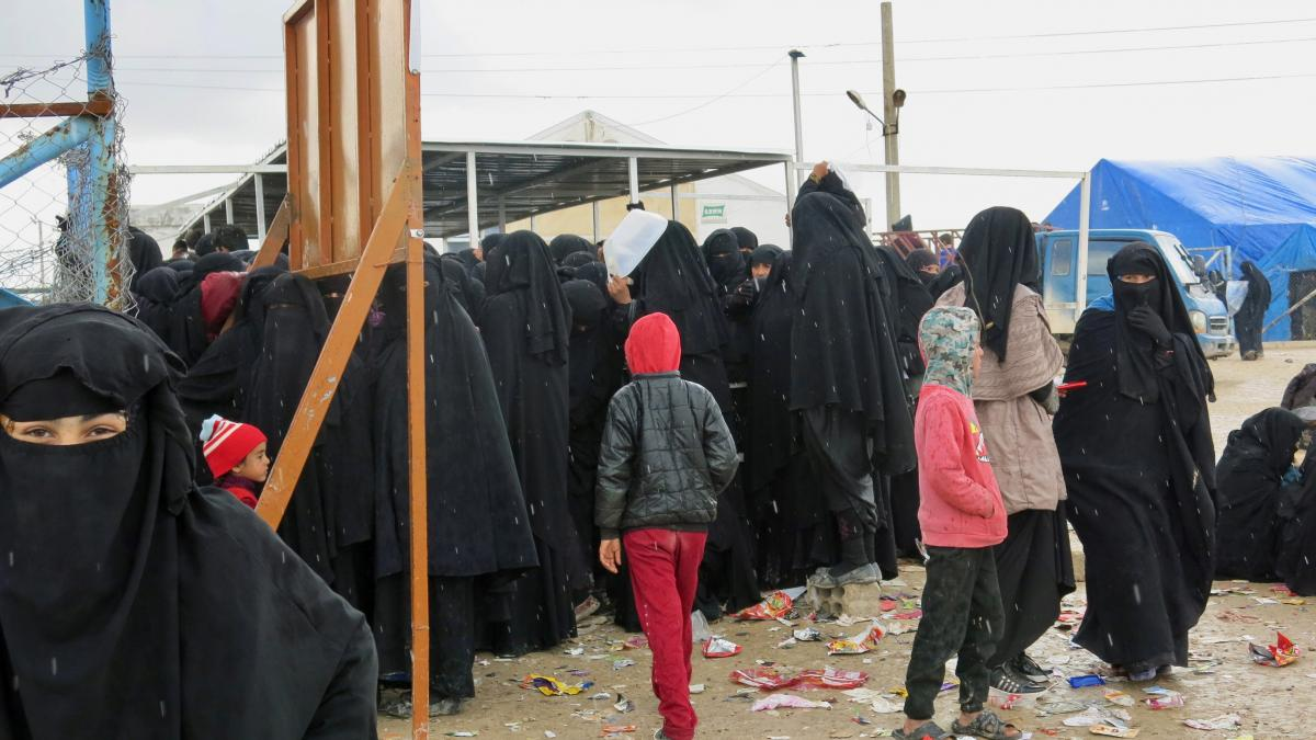 Women and children wait for distribution of food at the al-Hol camp in northeastern Syria. Most are family members of ISIS fighters, viewed by the region's Kurdish Syrian leadership as a potential danger. Iraq says it wants to bring back 30,000 of its cit