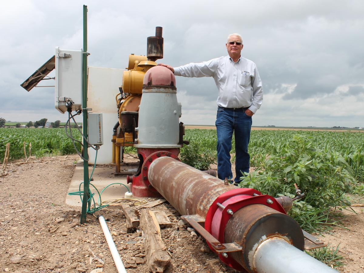 Jesse Garetson stands by one of his wells in Kansas. This one barely produces enough water to cool the engine, but many of Garetson's other wells pump more than 1,000 gallons of water per minute.