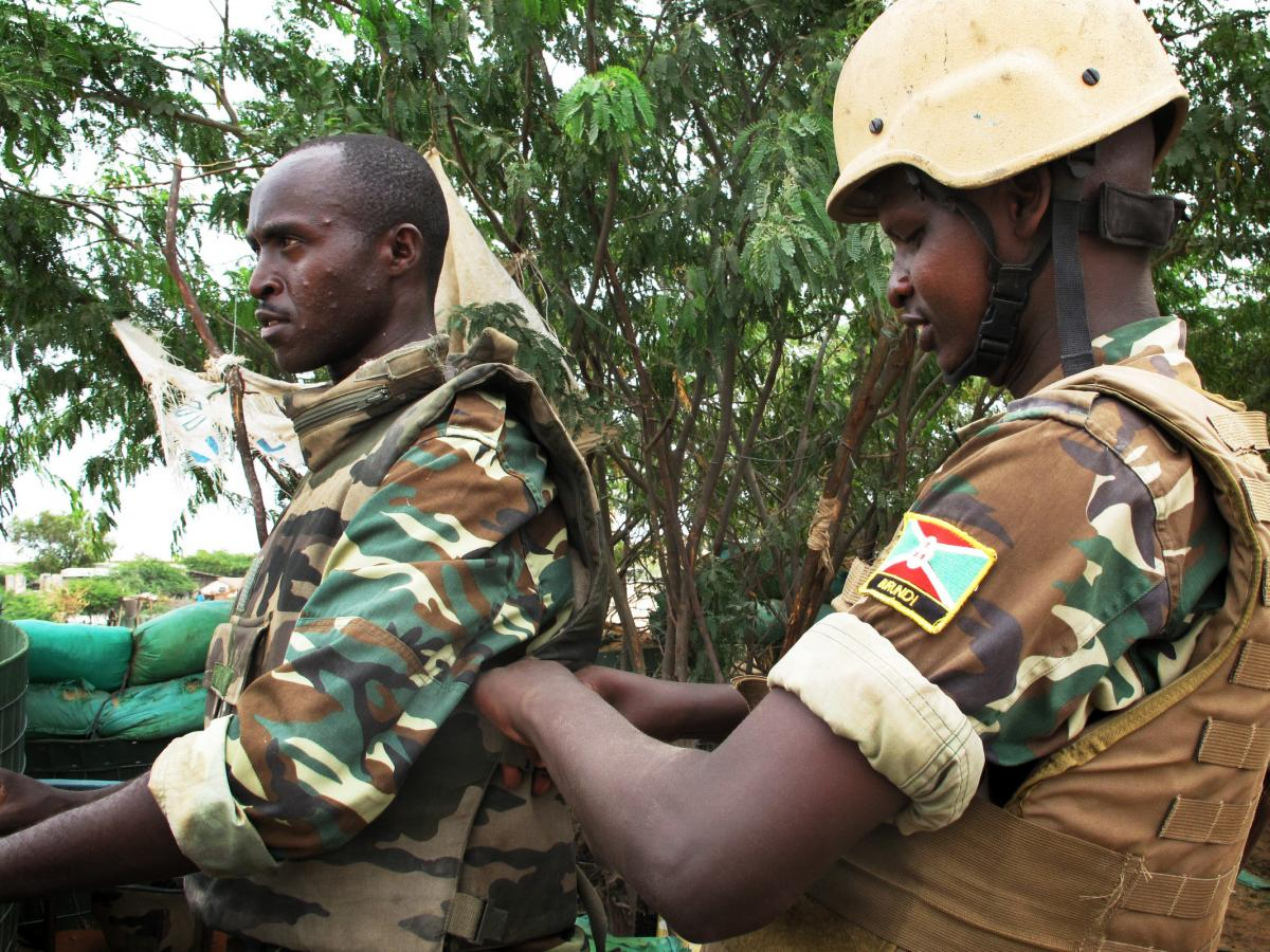 Burundian soldiers assist each other in putting on body armor in advance of their patrol in Somalia.