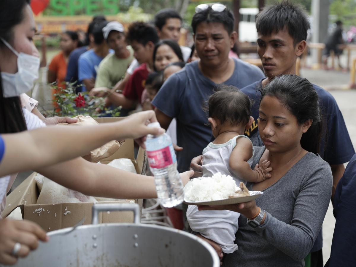 Evacuees receive a meal at an evacuation center at Santa Teresita, Batangas province, on Thursday.
