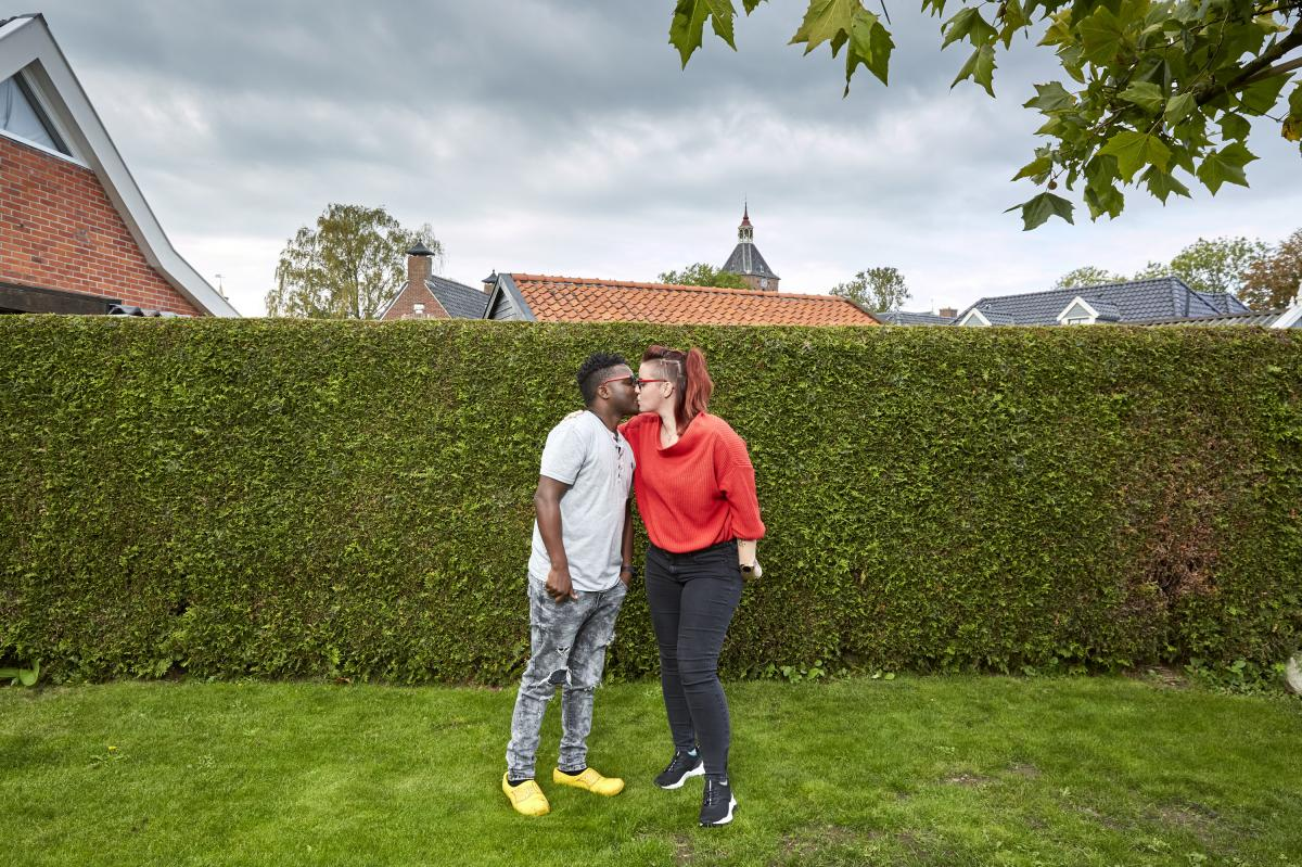 Patrick Phiri of Malawi and fiancée Fiona ten Have of the Netherlands kiss in her parents' garden. The couple met in Malawi, where they worked for the same charity, and fell in love. A three-week visit to the Netherlands turned into seven months because