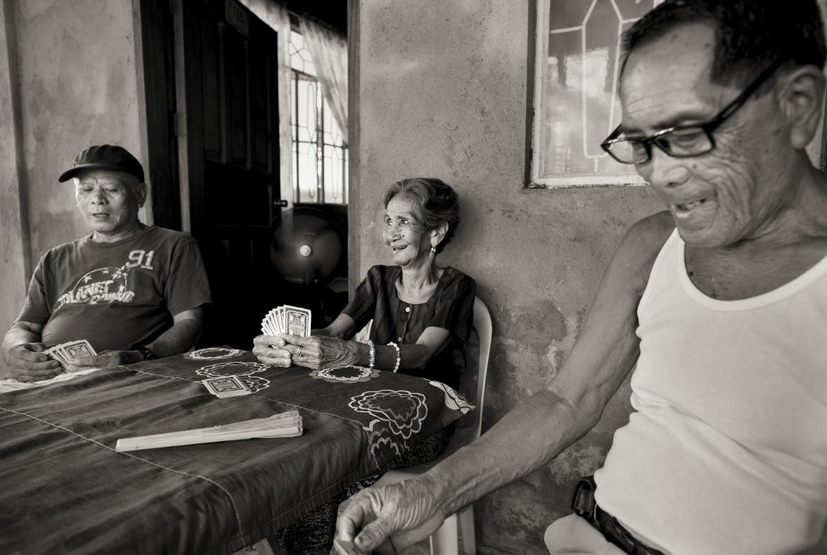 Emilia dela Cruz Mangilit, 92, center, plays a game of cards with her neighbors Abelardo Hernandez and Cezar Lalu, left and right. Mangilit was 15 years old when her village of Mapaniqui in Pampanga was shelled and then raided by the Japanese during World
