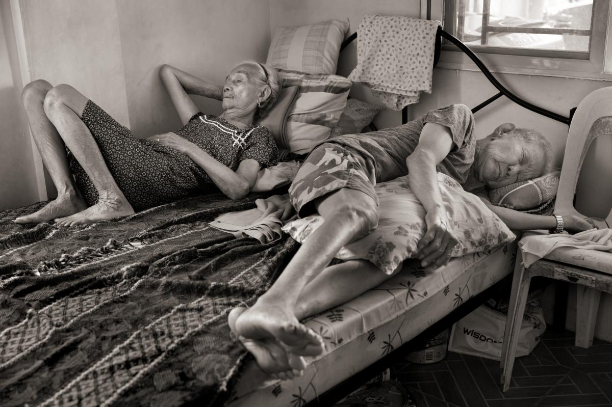Narcisa Claveria takes a midday nap with husband, Anaceto Claveria, in their home in Antipolo, Metro Manila. Claveria was 12 years old in 1943 when the Japanese came to their village in Abra, Philippines, during World War II. Accused of harboring guerrill
