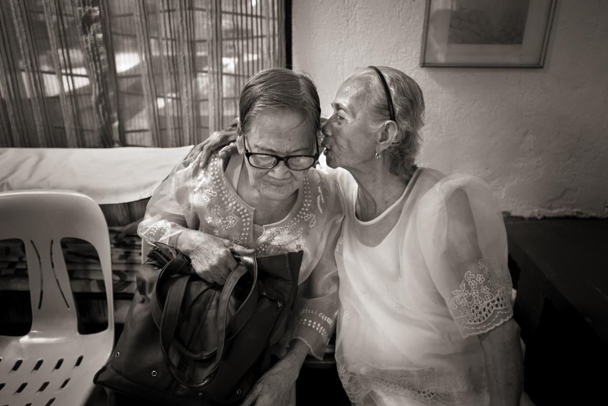 """Narcisa Claveria, right, whispers in Estelita Dy's ear as a group of """"comfort women"""" gather to celebrate Dy and Remedios Tecson's birthdays at the Lila Pilipina office in Quezon City on Saturday, April 27, 2019."""