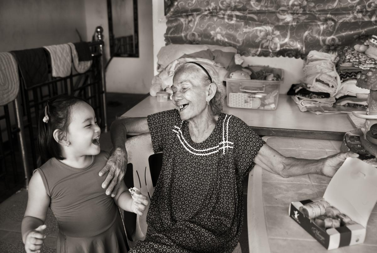 Narcisa Claveria shares a pastry with her great granddaughter, Atarah Mizsha Cancino, at the family's home in Antipolo, Metro Manila.