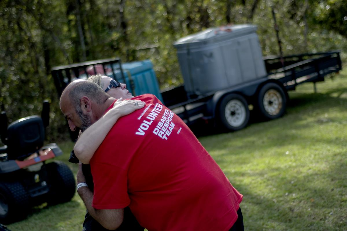 Operation BBQ Relief provides meals to displaced residents and emergency personnel during times of natural and other disasters. Above, David Marks, head of marketing for the group, shares a hug with a woman during relief operations in Wilmington, N.C., la