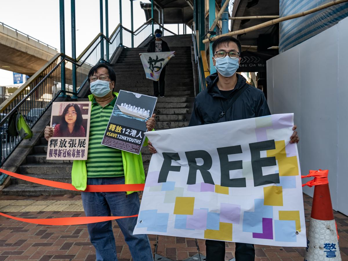 Pro-democracy activists hold placards in support of 12 Hong Kong residents detained in mainland China and former lawyer Zhang Zhan outside the Liaison Office of the Central People's Government on Dec. 28 in Hong Kong. They protested as Zhang  and the 12 r
