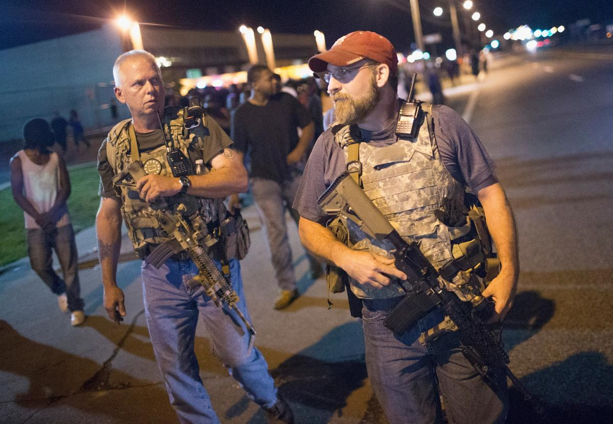 Reported members of the Oath Keepers walk along West Florissant Street as demonstrators mark the anniversary of the shooting of Michael Brown in August 2015 in Ferguson, Mo.