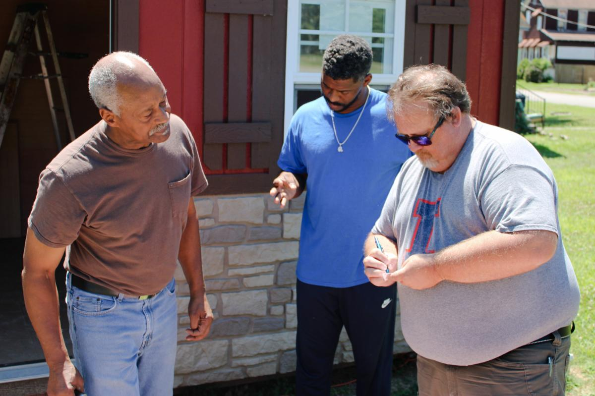 University of Illinois Extension director Jody Johnson (right) exchanges contact information with Lee Wright (left) and his son Roman. The Extension's office in southern Illinois has launched a vaccination education program that aims to reach this storied