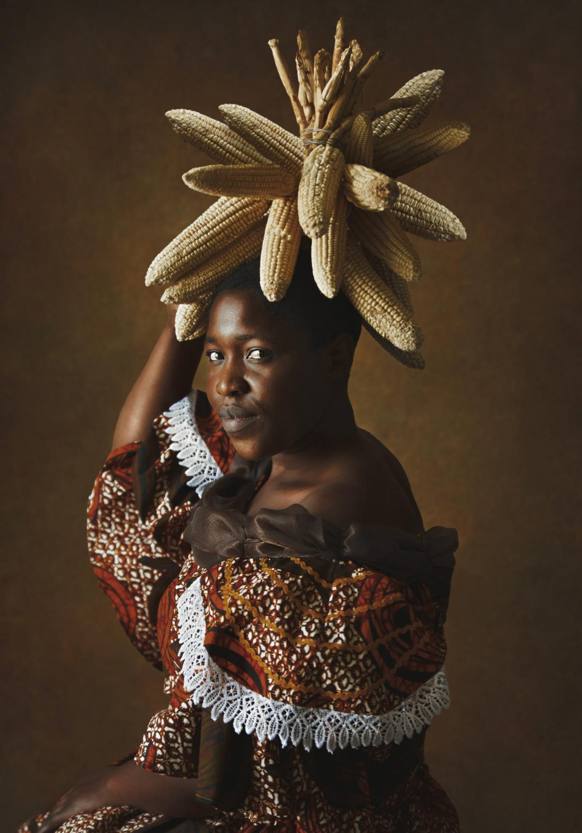 Lady With Corn. Kudita highlights corn in a headdress. A basic grain in Zimbabwe for centuries it still shapes daily meals.