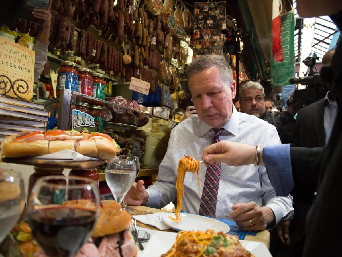John Kasich watches spaghetti spooned onto his plate at Mike's Deli on Arthur Avenue in The Bronx, N.Y.
