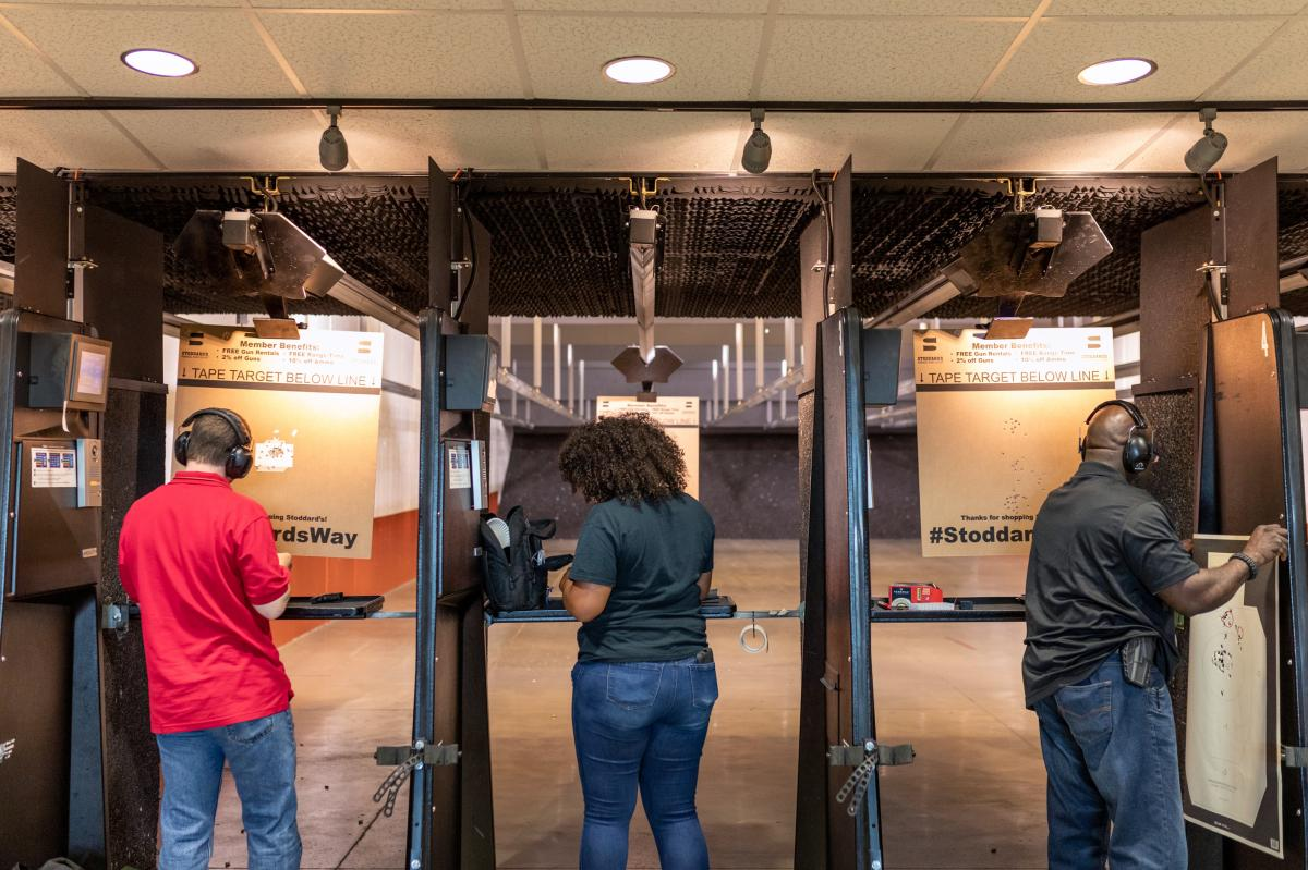 Michael Doyle (left), Casandra Light and Colin Mapp prepare to shoot and review their targets in a gun range in Atlanta.