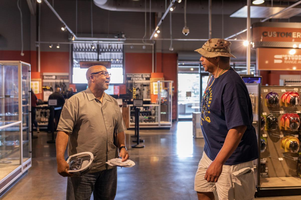 NAAGA president Philip Smith and Davis Nelson, a member of the Atlanta chapter, talk in the show room of Stoddard's  Range and Guns. Smith and others in the organization say the group is supportive of law enforcement. But also points out that carrying a g