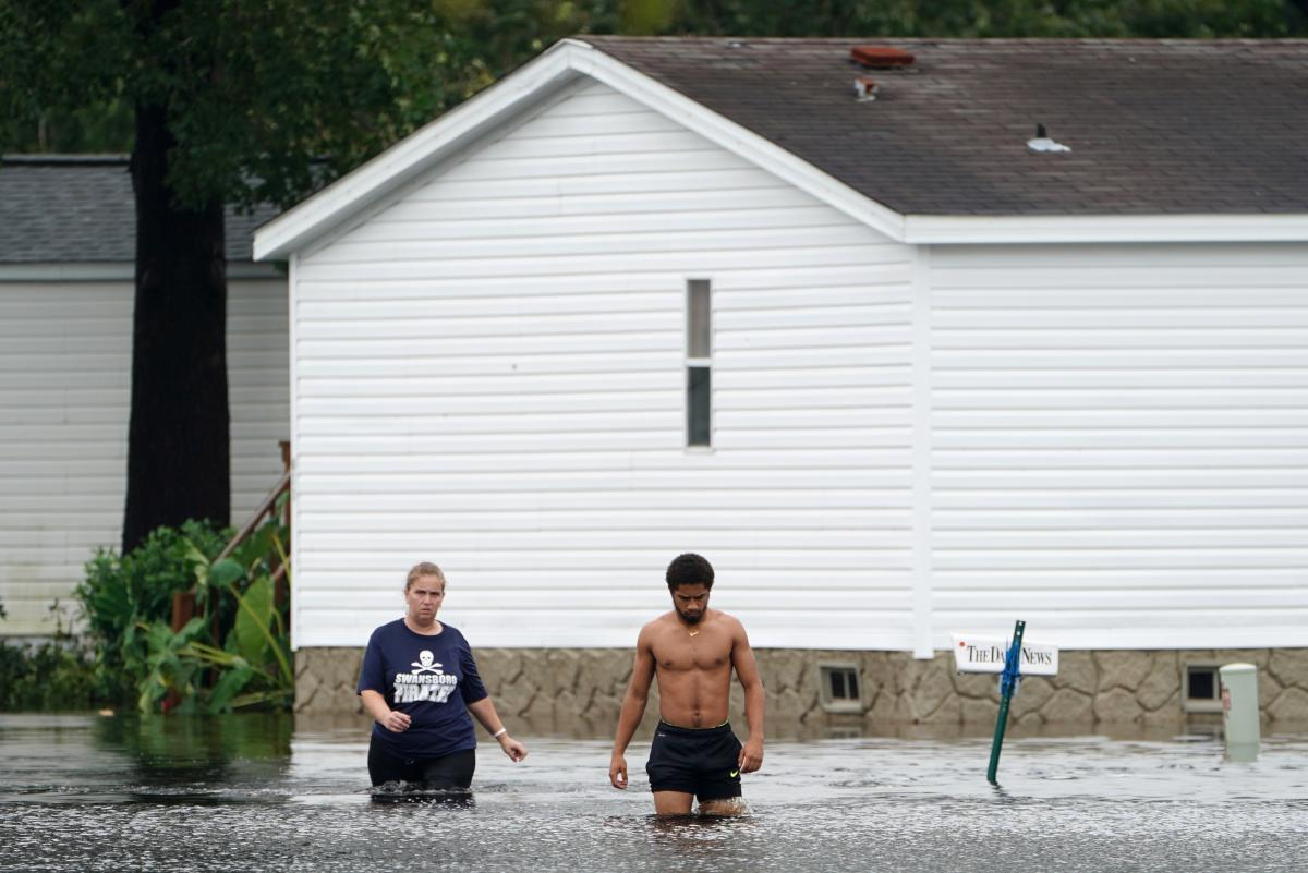 People walk through a flooded street Sunday after Florence struck Piney Green, N.C.