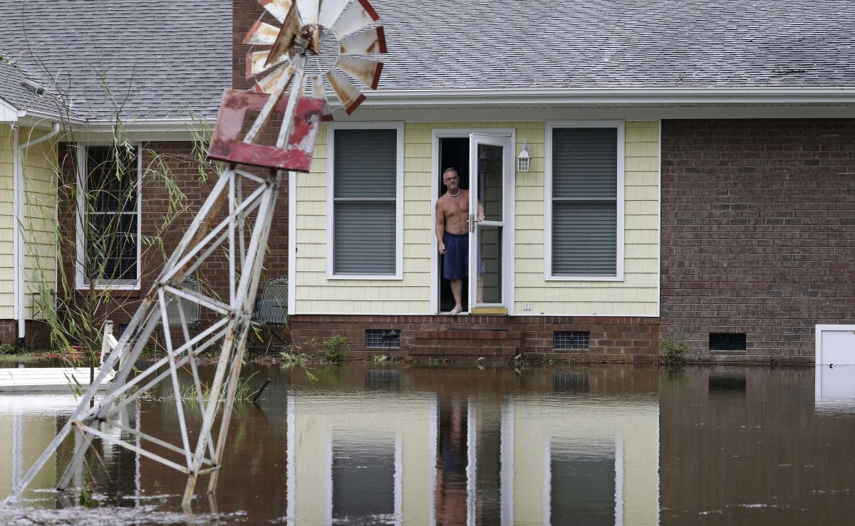 On Sunday, a man peers from his flooded home in Lumberton, N.C.