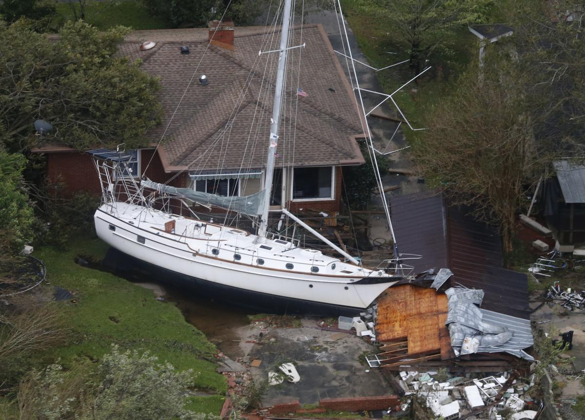 A sailboat is shoved up against a house and a collapsed garage Saturday after heavy wind and rain from Florence in New Bern, N.C.