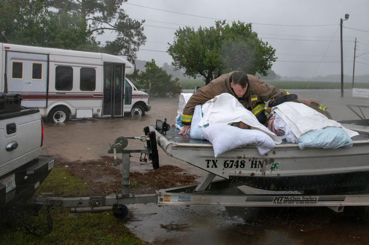 """A Lumberton firefighter on Saturday holds on to two nursing home patients as a member of the """"Cajun Navy"""" drives his truck during the evacuation of a nursing home due to rising flood waters in Lumberton, N.C."""