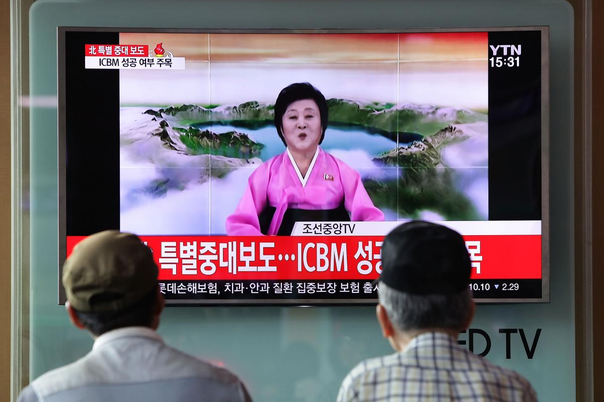People watch North Korea's state-run television in 2017 as presenter Ri Chun Hee announces that North Korea has test-launched its first intercontinental ballistic missile.
