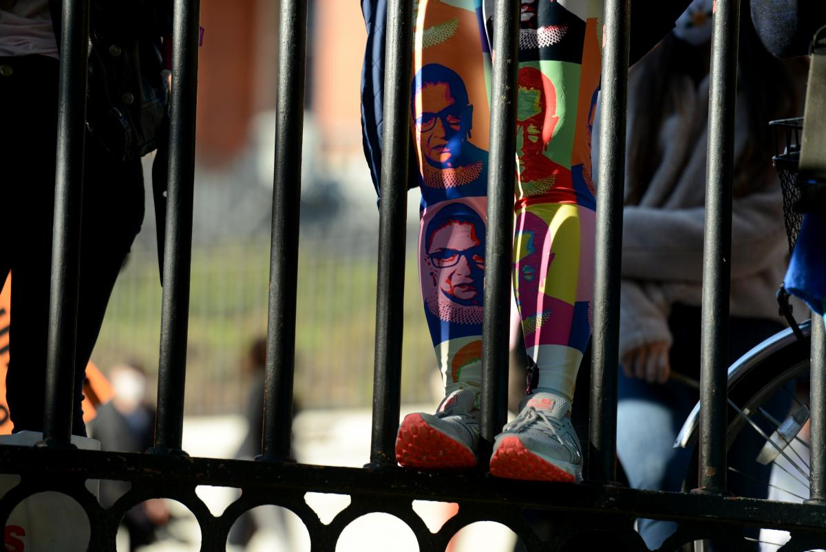 A woman wearing leggings featuring former Supreme Court Justice Ruth Bader Ginsburg scales a fence along the Boston Common.