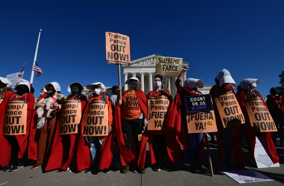 Women dressed as handmaidens to protest Supreme Court nominee Amy Coney Barrett.⠀