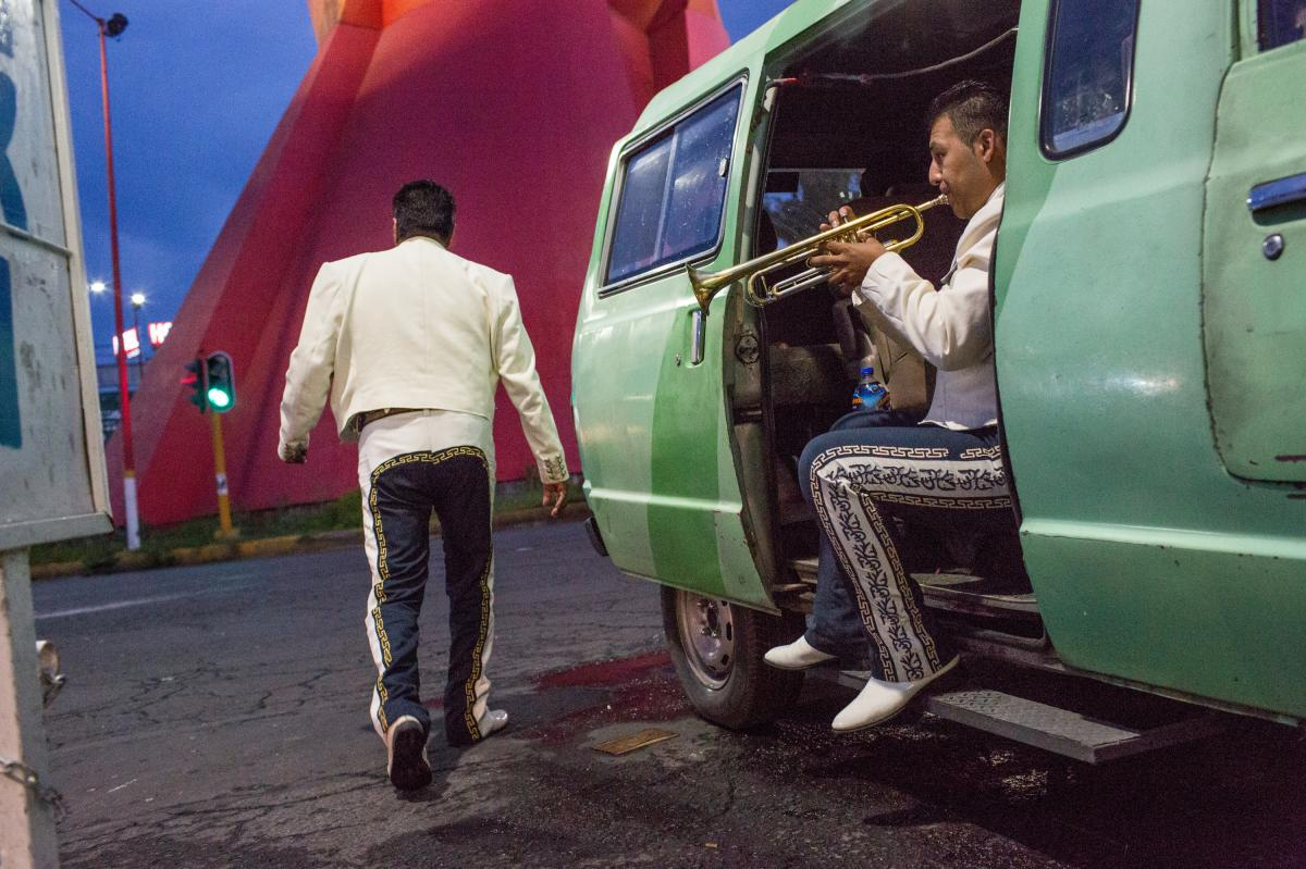 After a fight broke out nearby, Eric Giovani Fabian, 20, plays his trumpet, as his mariachi band, Nuevo Imperio, waits for clients in Mexico City, in August 2017.