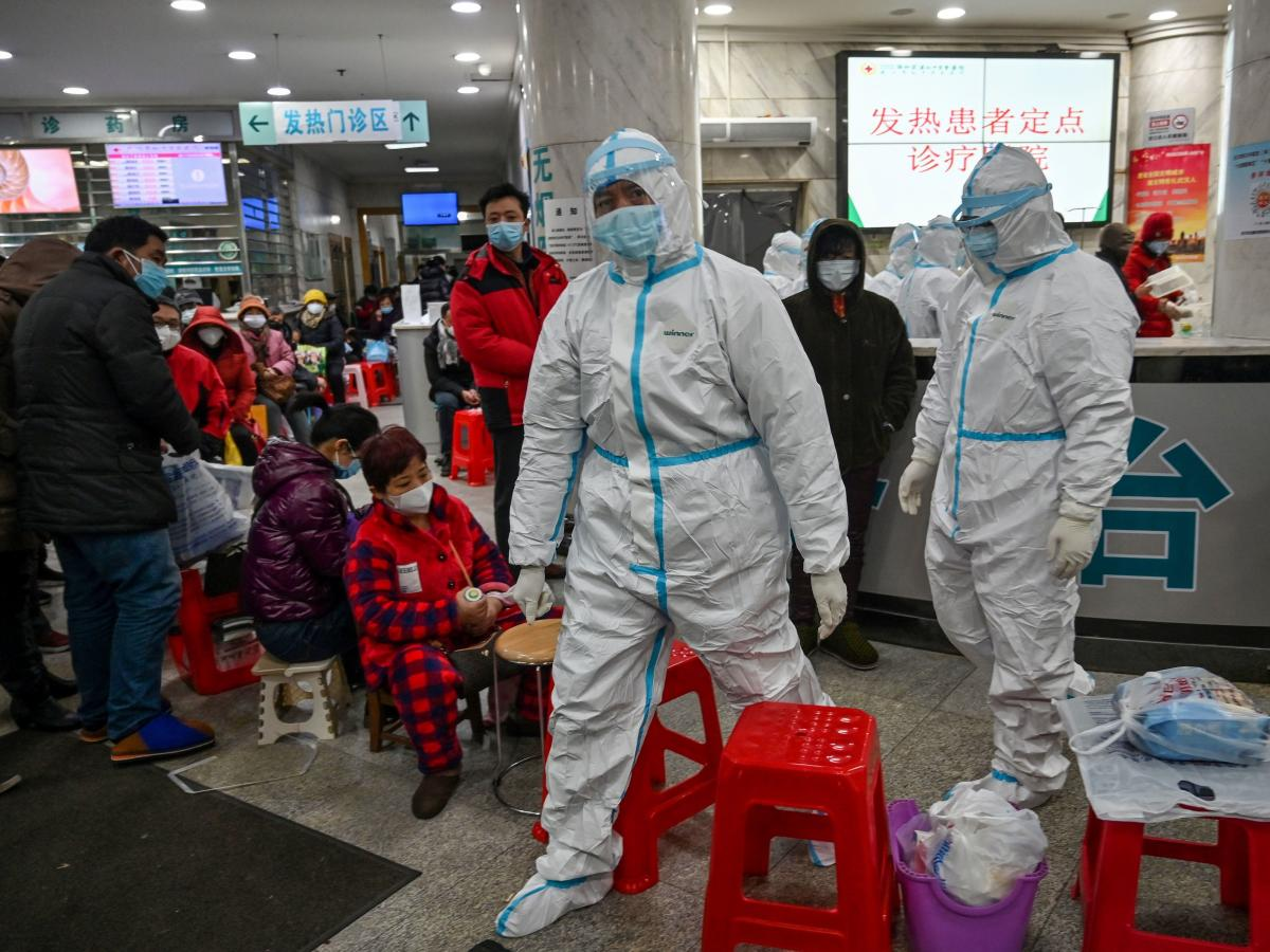 A scene from Jan. 25, 2020, in Wuhan: Health workers in protective garb walk next to patients awaiting medical attention at the Wuhan Red Cross Hospital.