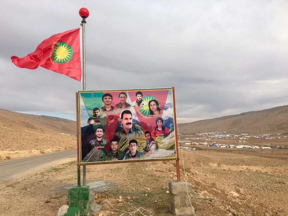 A flag of the Yazidis' Sinjar Resistance Units and photos of fighters killed battling ISIS on the side of the road in Sinjar, in northern Iraq. The pictures show slain fighters from both the resistance units and a Turkish Kurdish guerrilla group that back