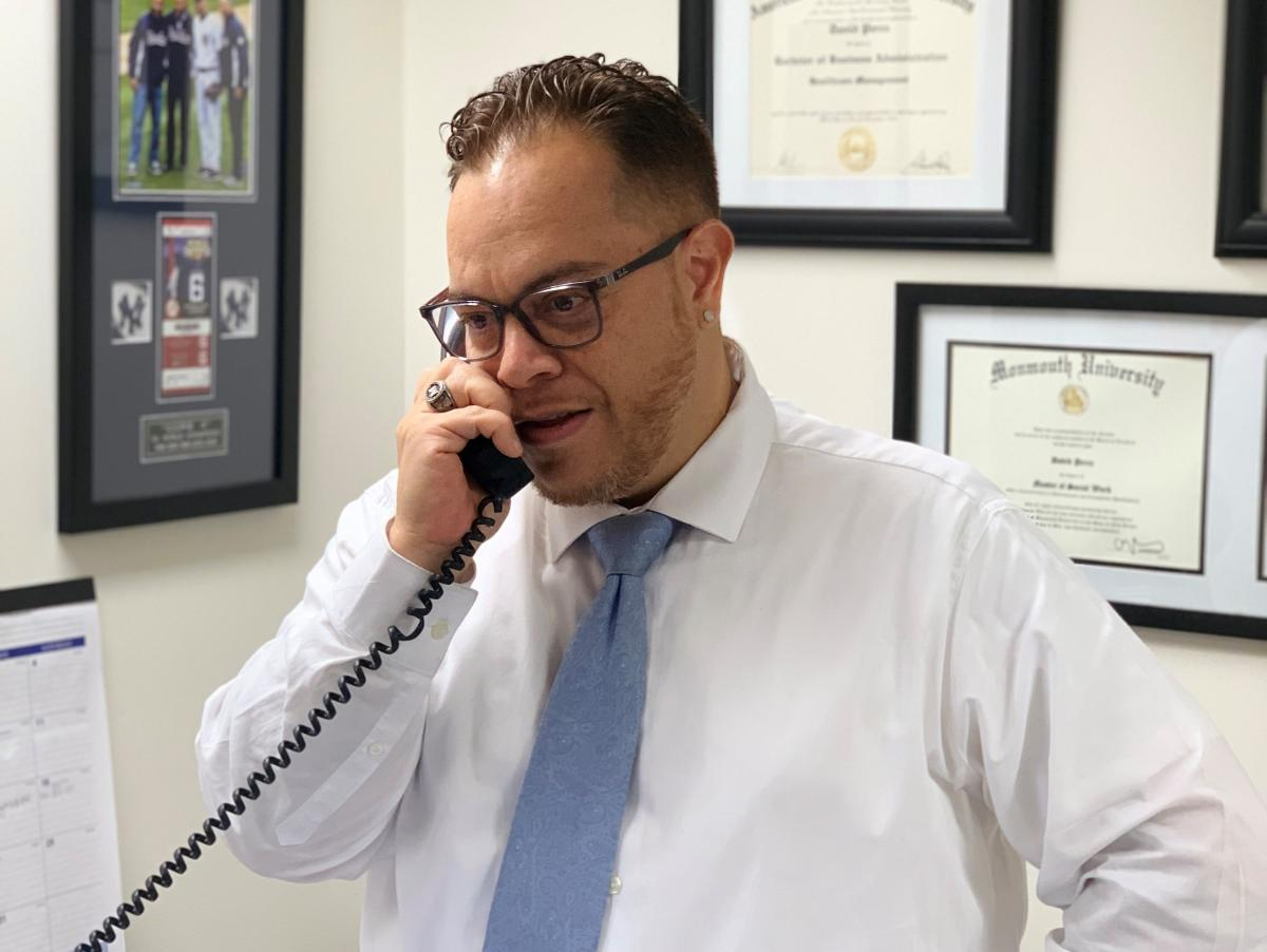 David Perez takes a call earlier this year in his office at the Long Branch Free Public Library. The U.S. Army veteran says he was surprised when his school advisers suggested he work there — but after several years in the job, he says it makes perfect