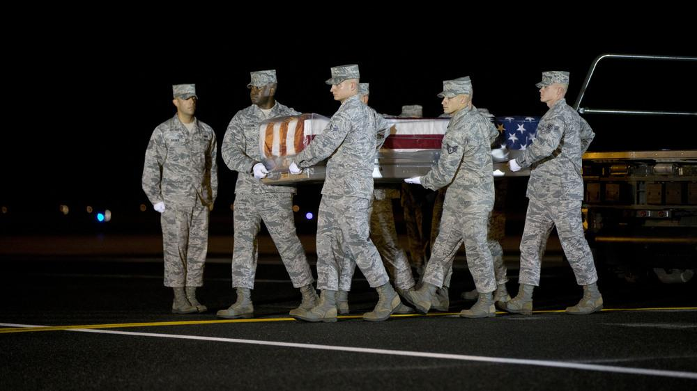 An Air Force team carries the transfer case with the remains of Maj. Phyllis J. Pelky, on Tuesday at Dover Air Force Base, Del. Pelky, 45, was killed two days earlier in a helicopter crash in Afghanistan. Though the U.S. formally ended its combat role in
