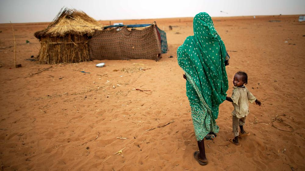 A woman and her daughter walk at the Zam Zam camp for internally displaced people in North Darfur, Sudan, in June 2014. The U.S. and other countries have said that Sudan is committing genocide in Darfur, and the United Nations has an ongoing peacekeeping