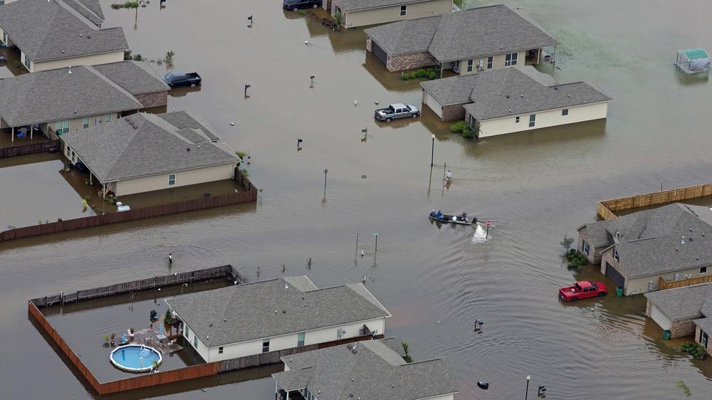 In this aerial photo a boat motors between flooded homes on Saturday after heavy rains in the region in Hammond, La.