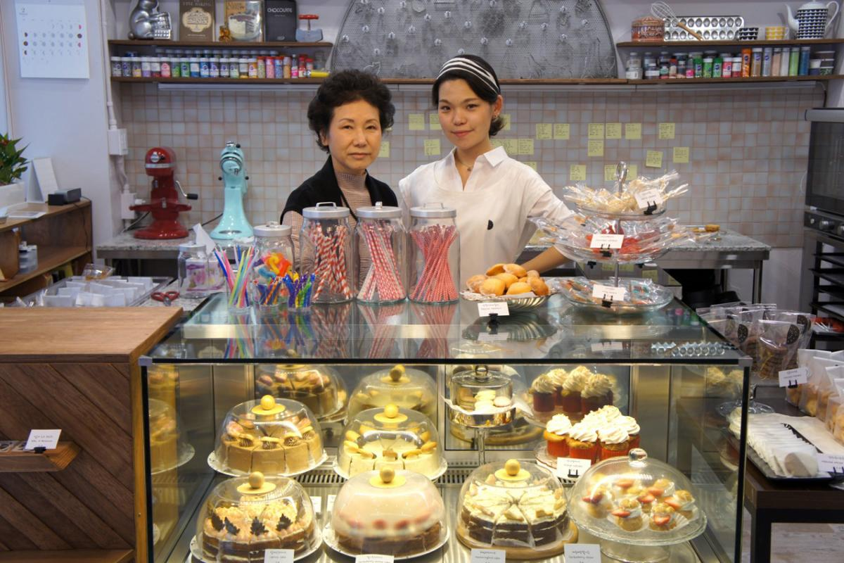 In this photo, Younghwa Chun (left) and Euni Cho celebrate the opening of Sweet Studio Dal D patisserie in Seoul, South Korea, in 2017. Chun was a toddler when her family fled North Korea, and doesn't have memories of life there.