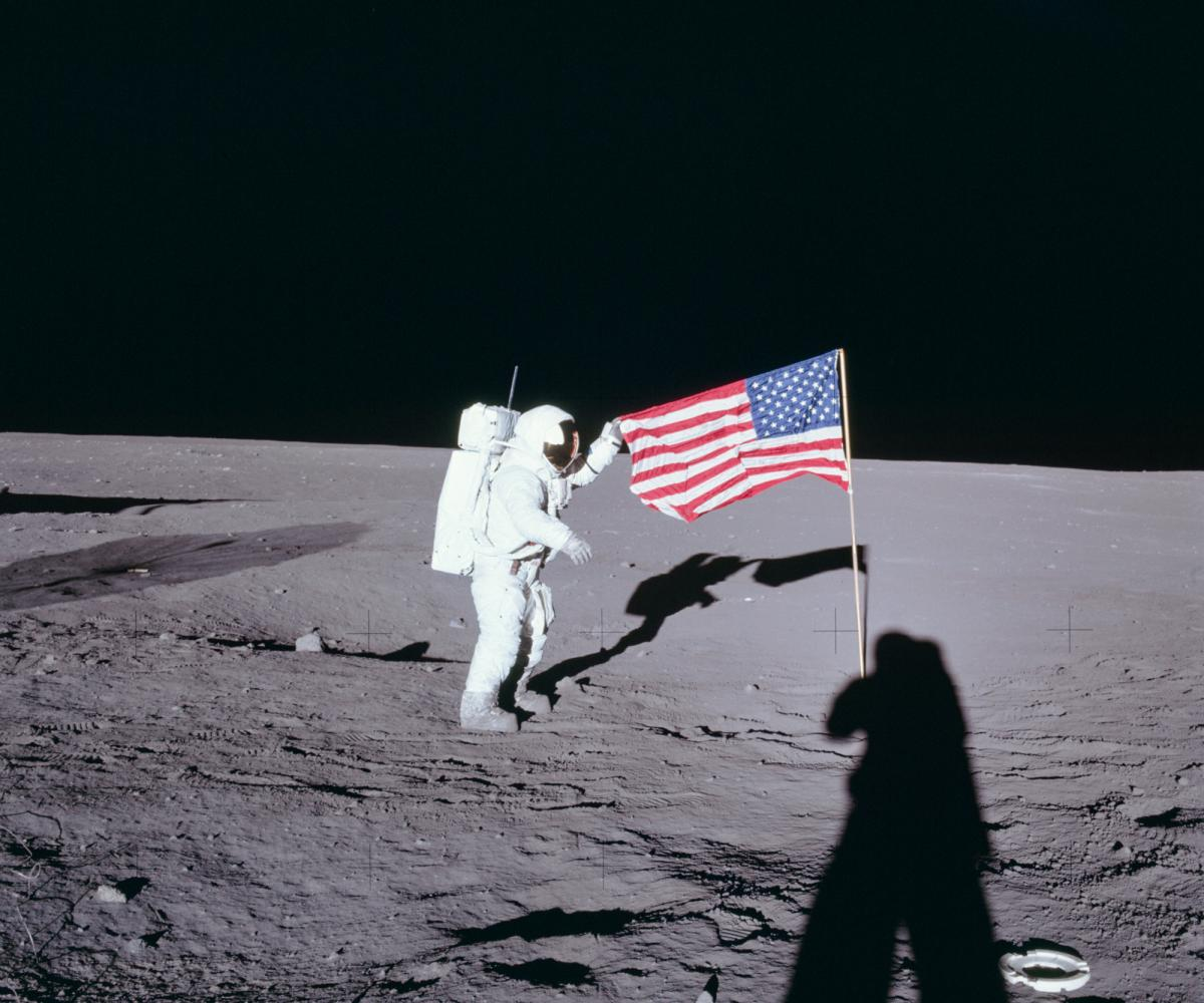 """From NASA: Apollo 12 commander Charles """"Pete"""" Conrad unfurls the United States flag on the lunar surface during the first extravehicular activity on Nov. 19, 1969."""