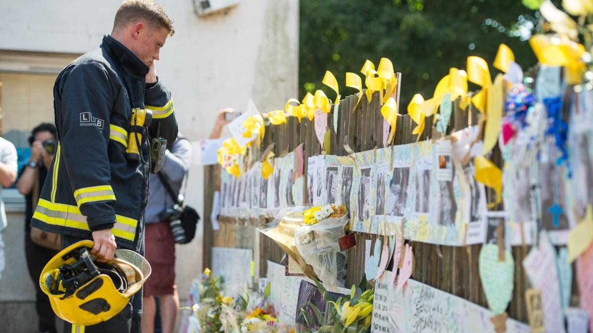 A firefighter looks at tributes to presumed victims of the Grenfell Tower fire, after observing a minute's silence at a community center near the apartment building in west London.