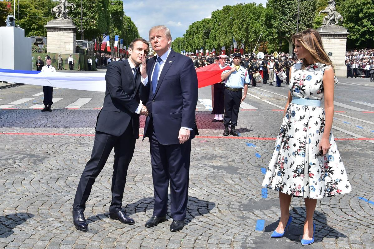 French President Emmanuel Macron (left) shakes hands with President Trump, next to first lady Melania Trump, during the annual Bastille Day military parade in Paris on July 14, 2017. Trump is hosting Macron in Washington this week for the first official s