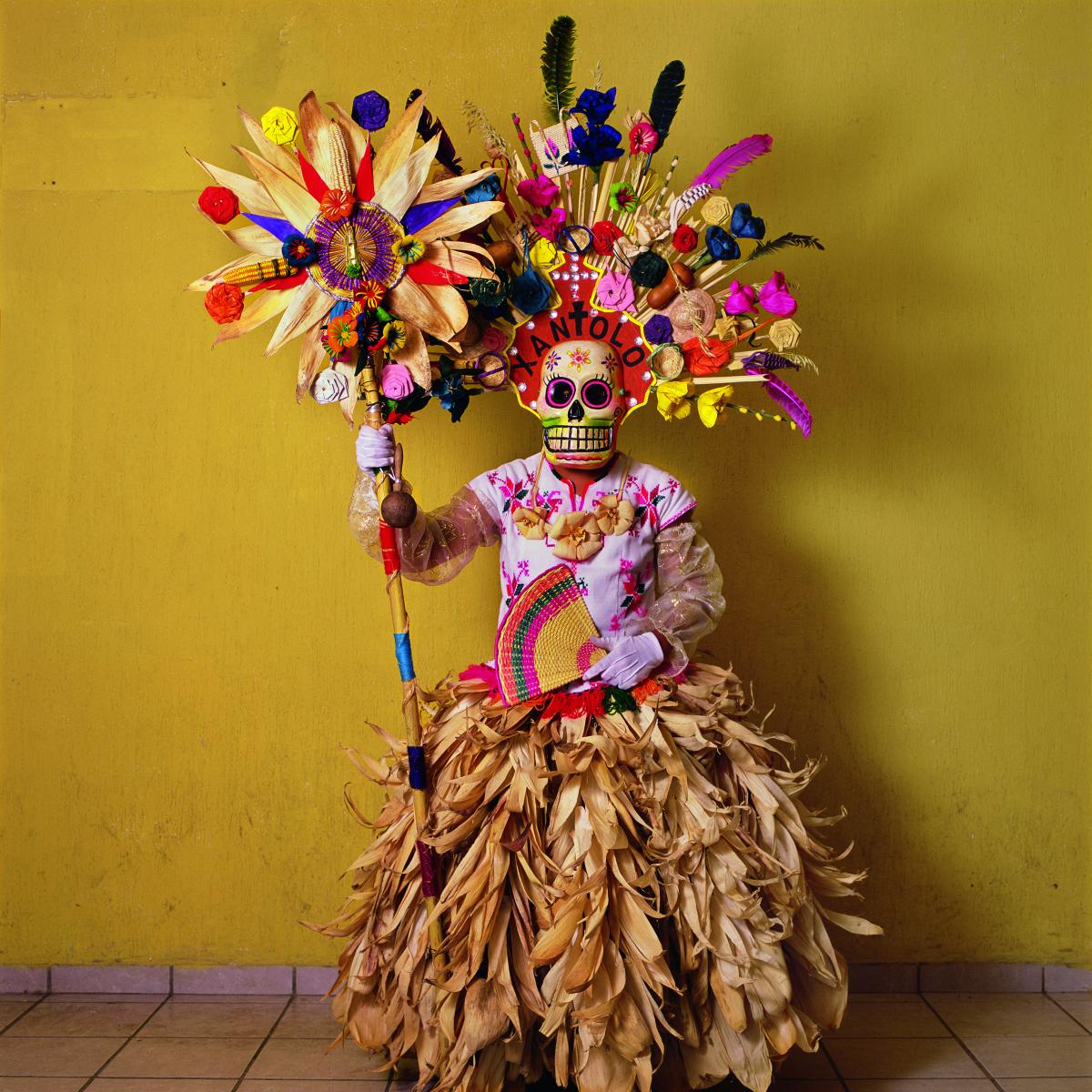 This costume, with corn husks and feathers and paper flowers, is worn by a member of a dance group that gathers in cemeteries and other places to mark Day of the Dead festivities (called Xantolo, the word written above the mask). The idea of combining a s
