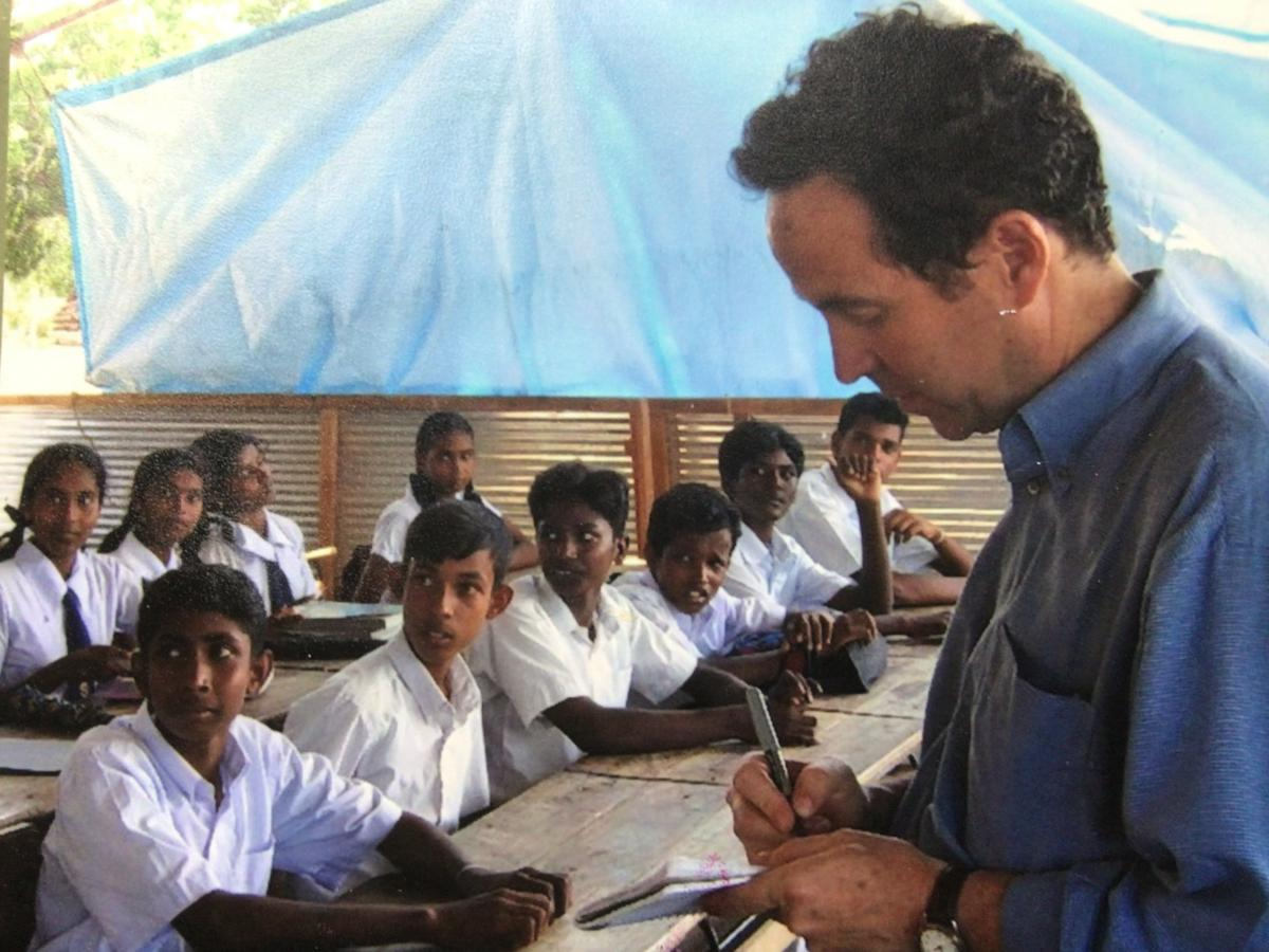 """Joel Charny, who's been a humanitarian aid worker for 40 years, talks to students at a camp for internally displaced people in northern Sri Lanka in 2005. It's one of his favorite photos, he says, """"because this is what I did hundreds of times: interview p"""