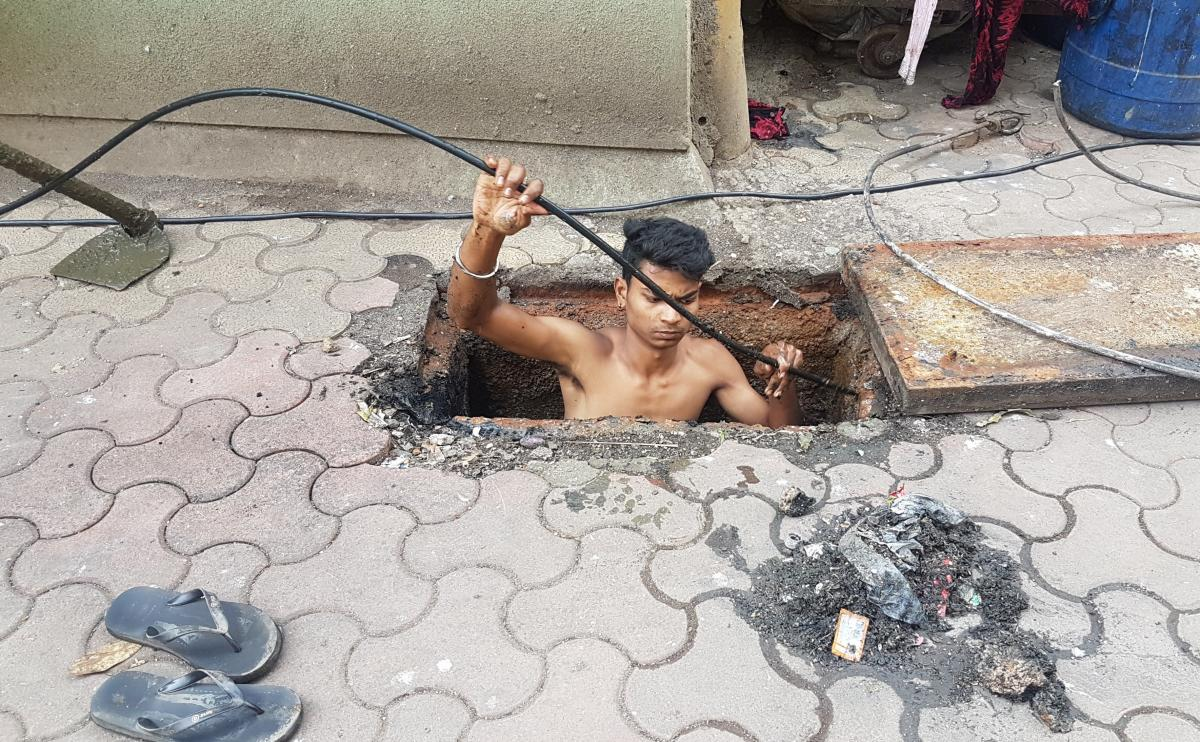 Jitesh Singolia, 19, climbs down a manhole to clean sewer pipes using his bare hands.