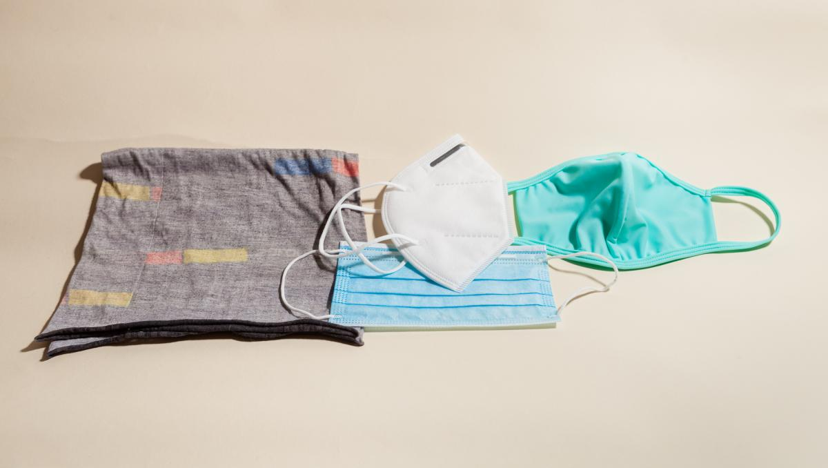 Left to right: a neck gaiter (aka a buff) that slips over the head; a KN95 respirator, a version of the N95 respirator used in U.S. hospitals; a pleated surgical mask (below the KN95); a cloth mask.
