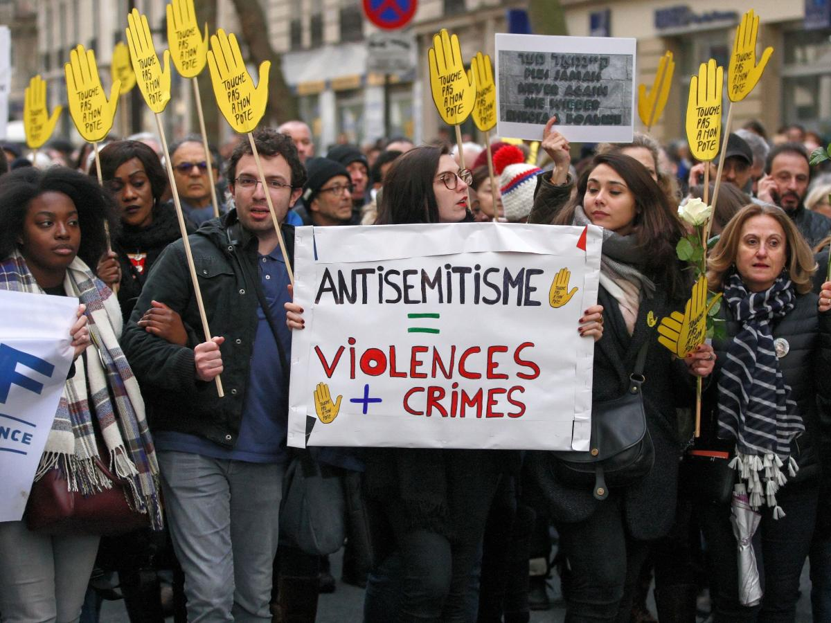 Demonstrators hold signs against anti-Semitism during a silent march in Paris on March 28 in memory of Mireille Knoll, an 85-year-old Jewish woman murdered in her home in what police believe was an anti-Semitic attack. Knoll escaped the mass deportation o