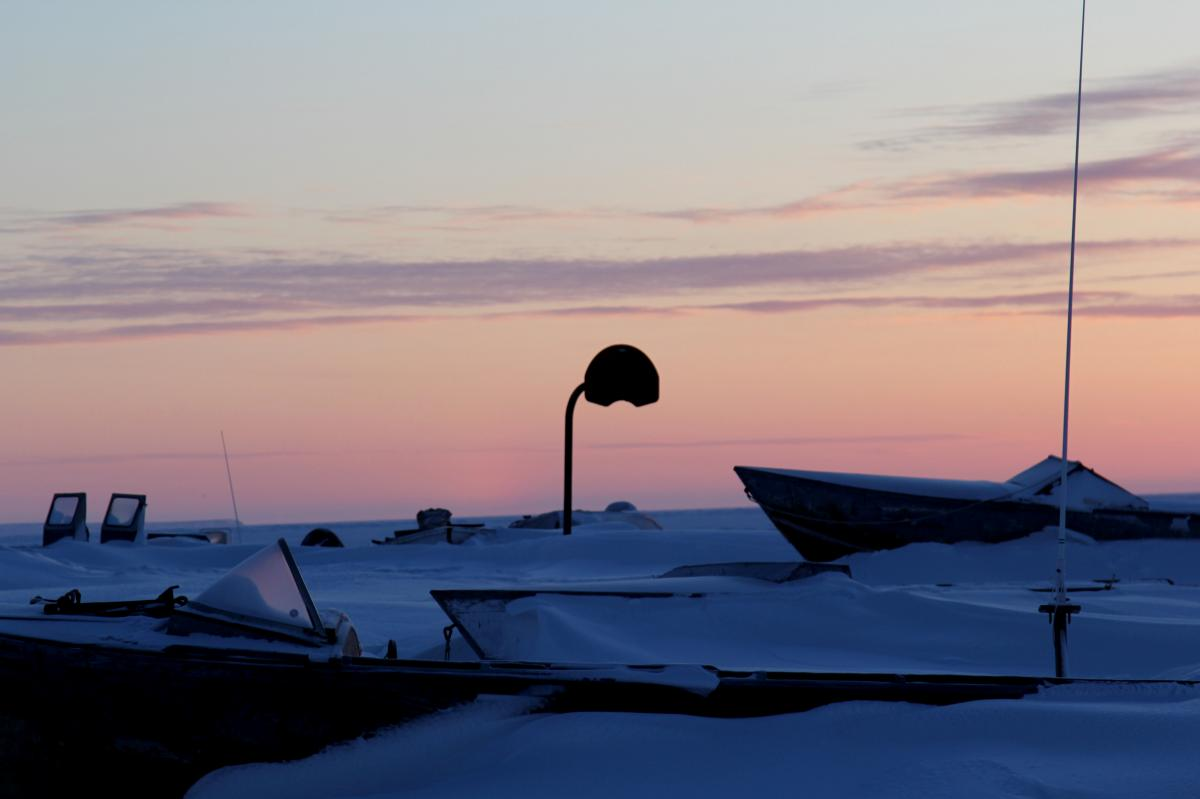 Basketball hoop near boats buried in the winter snow. Shishmaref is just a few dozen miles below the Arctic Circle, and in the depths of winter the sun rises close to noon.