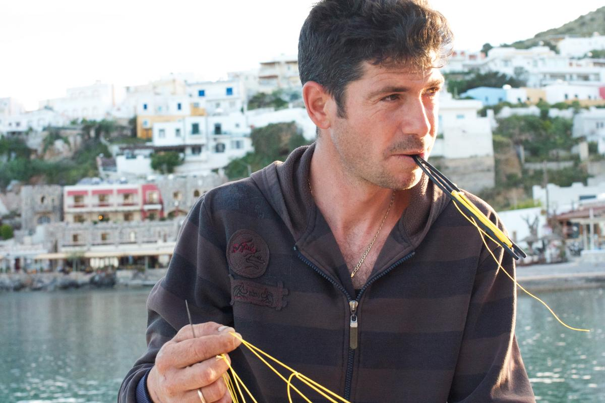 """Parisi Tsakirios, 29, mends a net as he prepares for another fishing trip. """"I can't imagine doing any other job, because I love the sea,"""" he says. """"But there are hardly any fish. I barely break even. I can't support my family."""""""