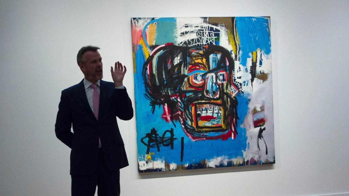 Jean-Michel Basquiat's untitled painting of a skull is displayed behind an official with Sotheby's, which offered the media a preview earlier this month. On Thursday, the work sold for $110.5 million — the highest sum ever paid at auction for a work by