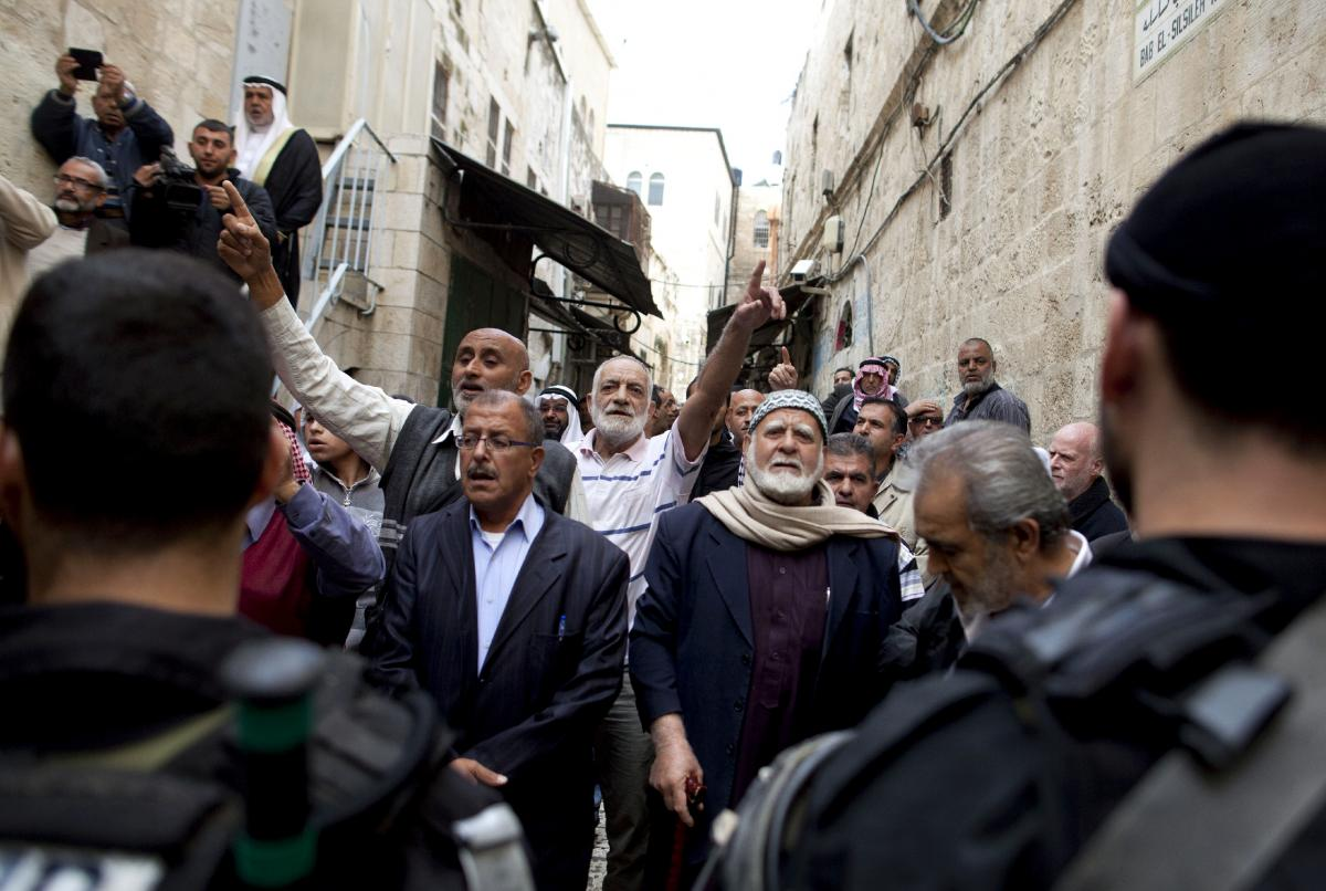 Palestinian men shout slogans next to Israeli police as they await permission to enter what Jews call the Temple Mount and Muslims call the Nobel Sanctuary, on Nov. 5, in Jerusalem, Israel. On Friday, Israel dropped age restrictions on men attending Frida